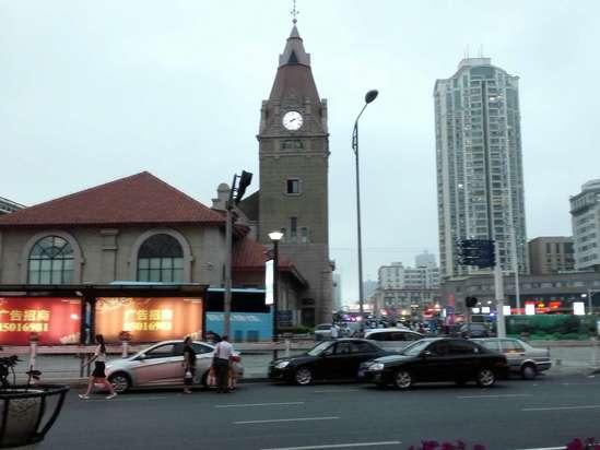 青岛火车站位于青岛市中心,距离海边仅两百多米。这是一组建于1899年的德国文艺复兴风格建筑,它拥有醒目的红瓦黄墙,以及一座尖顶的钟楼,外形很漂亮也很文艺。青岛火车站至今仍在使用,是青岛的地标建筑之一。 青岛火车站主要由钟楼和候车大厅两大部分组成。它是由德国人魏尔勒和格德尔茨设计的,这坐火车站再现了设计师家乡的建筑风格,尤其是35米高的车站钟楼,更是沿用了德国乡间教堂样式。一百多年间,车站钟楼上行走的时钟一刻不停地记录了那些行色匆匆的旅客们。