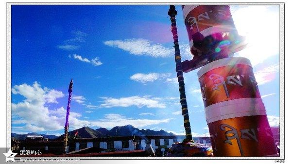 在大昭寺前 映入我心的是这样的画面 蔚蓝色的天空上 有一轮朦胧的