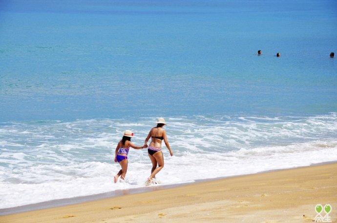 母亲带着年幼的男孩子,站在海天相接地方,鼓励孩子要勇敢的面对海浪.